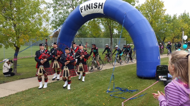 Members of the Pipes & Drums of Edmonton Police Service lead the cyclists of Tour du Cancervive 2015 across the finish line in Edmonton.
